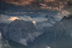 Sexten Dolomites in clouds illuminated by setting sun in Italy Royalty Free Stock Photos