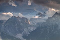 Sexten Dolomites in clouds illuminated by setting sun in Italy. Sexten Dolomites in sunlit clouds at sunset with Drei Zinnen Tre Cime di Lavaredo, Einserkofel Royalty Free Stock Image