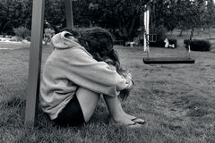 Sexual Assault. Concept photo of sexual assault - traumatized young woman sit on the grass of a playground Stock Images