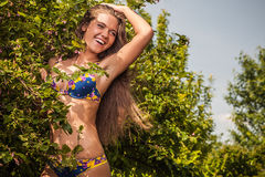 Sexual beauty dressed bikini poses in an summer garden. Royalty Free Stock Image
