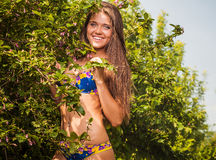 Sexual beauty dressed bikini poses in an summer garden. Royalty Free Stock Photo