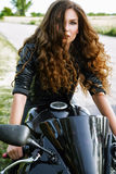 Sexual biker woman with her sport motorcycle royalty free stock photo
