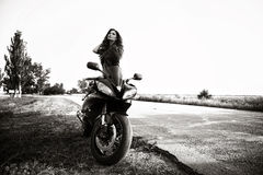 Sexual biker woman with her sport motorcycle stock images