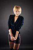 Sexual blond woman in short skirt . Black background royalty free stock photos