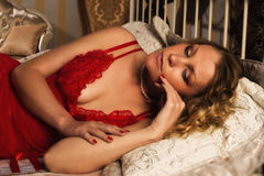 Sexual blonde in red lying on a bed Stock Photography