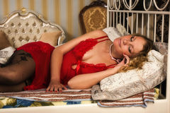 Sexual blonde in red lying on a bed Royalty Free Stock Image