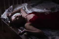 Sexual blonde in red lying on a bed Stock Photos