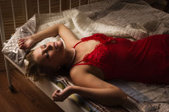 Sexual blonde in red lying on a bed Stock Images