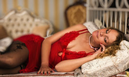 Sexual blonde in red lying on a bed Royalty Free Stock Photos