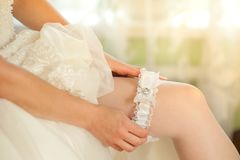 Sexual bride putting on wedding garter. Bride`s hands royalty free stock image