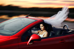 Sexual bride riding in a red sports car Stock Photos