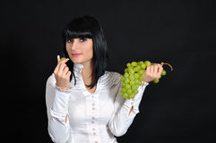 The sexual brunette with grapes Stock Image