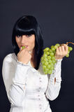 The sexual brunette with grapes Stock Images