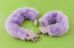 Sexual cuffs with purple fur. On a green background stock images