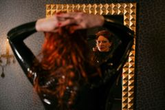 Sexual fetish redhead woman wearing black latex rubber catsuit and looking at the mirror in dark room. Alone stock photography