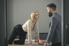 Sexual flirt at work. secretary seduce boss in office. Businesswoman on desktop look at bearded businessman. Man royalty free stock images