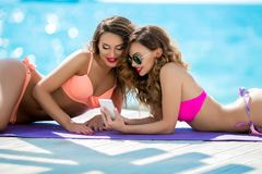 Sexual girl in a bright bikini on a sunny beach. Bikini, red lips, blue sea, tanned girl. Two friends have a rest on the. Sea, make selfie, use a mobile phone royalty free stock photography