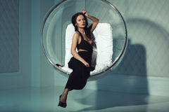 Sexual girl with dark hairs, sitting on a round chair Royalty Free Stock Image