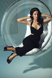 Sexual girl with dark hairs, sitting on a round chair Stock Photography