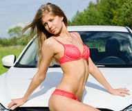 The sexual girl in pink bikini with white car Stock Images