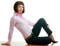 Sexual girl in trousers. Sitting on the desk in the office Royalty Free Stock Image