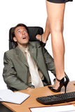 Sexual harassment. Sexy woman standing on desktop before businessman on a white background Stock Images