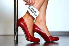 """Sexual harassment alert. With young woman with red high heels shoes showing a note with the text """"sexual harassment Royalty Free Stock Photo"""