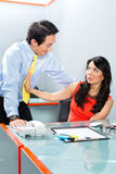 Sexual harassment by boss in Asian office Royalty Free Stock Images