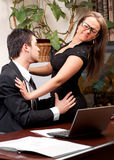 Sexual harassment at work. Young business man sexually harassing woman in office Stock Image