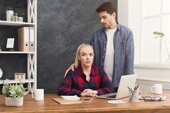 Sexual harassment at work , copy space. Sexual harassment at work, lustful colleague touching young shocked women in office, copy space Royalty Free Stock Photography