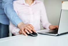 Sexual harassment at work. Man touching secretary`s hand Royalty Free Stock Image