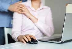 Sexual harassment at work. Man touching secretary`s shoulder Royalty Free Stock Photo