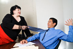 Sexual Harrassment. A female office worker makes sexual advances to a young mail coworker Stock Image