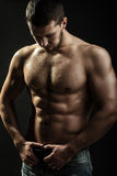 Sexual muscular man. One handsome sexual strong young man with muscular body in blue jeans holding hands on torso standing in studio on black background royalty free stock image