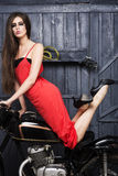 Sexual slim young girl on motorbike. Sexual slim young girl with bright make up in long beautiful red dress looking forward sitting on old motorbike in garage on Royalty Free Stock Photo
