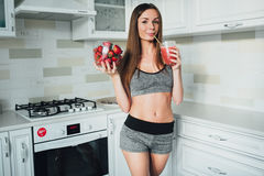 Sexual sports girl holding a bowl of strawberries and a glass of smoothie in the kitchen. Stock Photo