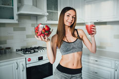 Sexual sports girl holding a bowl of strawberries and a glass of smoothie in the kitchen. Stock Image
