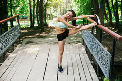 Sexual sports girl playing sports outdoors. She performs a variety of exercises Royalty Free Stock Images