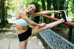 Sexual sports girl playing sports outdoors. She performs a variety of exercises Royalty Free Stock Photos