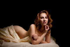 Sexual woman in boudoir shooting lying on bed Stock Photography