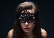 Sexual woman in lace mask. On black background stock photography