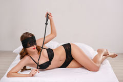 Sexual woman lying on bed and holding leather whip Royalty Free Stock Images