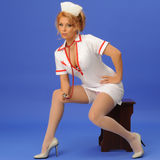 Sexual woman in nurse suit with stethoscope blue backgroundSto Royalty Free Stock Image