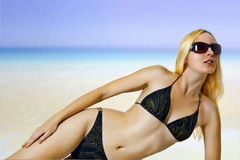 Sexual woman on sea beach in bikini sunbathing Royalty Free Stock Photography