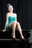 Sexual woman in short mini blue dress sitting on the piano Royalty Free Stock Images