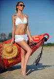 The sexual young blonde woman with a beautiful body posing on a beach in a white bathing suit against the ocean Royalty Free Stock Photo