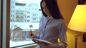 Sexual young brunette secretary in short with blue stripes standing near the wide window and makes notes stock footage