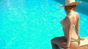 Sexual young lady in straw hat and seductive swimsuit sits by the blue pool stock video