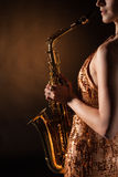 Sexual young woman posing with saxophone at studio. Portrait of sexual young woman posing with saxophone at studio Royalty Free Stock Photos