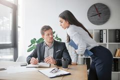 Sexual young woman lean to table. She looks at her boss. Young man sit at table and look at her breast. Guy is excited. Sexual young women lean to table. She stock photo